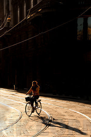 A woman riding a bicycle in Milan.