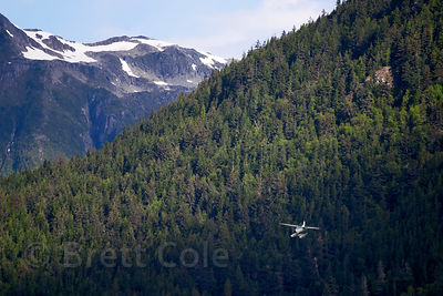 A small plane flies past high granite peaks in the Great Bear Rainforest, British Columbia