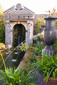 Rill pool flanked by turned oak urns spouting water through gilded lions' heads, with golden agaves in their tops. Planting includes Alchemilla mollis and white agapanthus. Water emerges from a rocky grotto framed by a scallop shell pediment and muscular caryatids. The Collector Earl's Garden designed by Julian and Isabel Bannerman. Arundel Castle Gardens, Arundel, West Sussex, UK