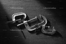Clamp compression tool piled diagonally on wooden background