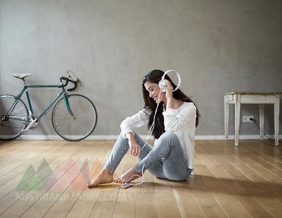 Smiling woman sitting on wooden floor at home listening music with headphones