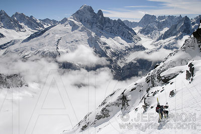 Skier climbing a slope opposite the Mont Blanc Massif