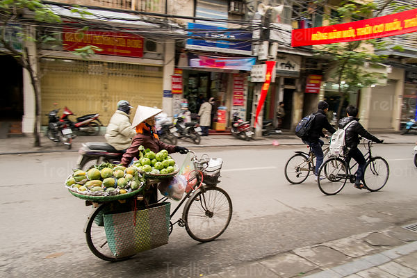 Vietnamese papaya street vendor with bicycle on the road in Hanoi
