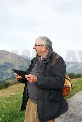 Senior man with digital tablet hiking in the mountains looking at directions.