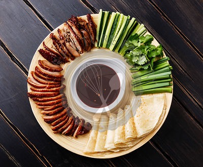Sliced Peking Duck served with fresh cucumber, green onions, cilantro and roasted wheaten chinese pancakes with Hoysin sauce on black wooden background