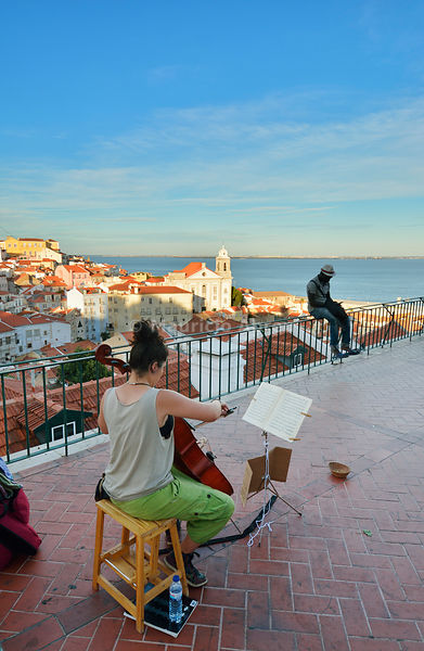 A musician plays overlooking Alfama at Portas do Sol belvedere. Lisbon, Portugal