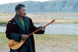 A Kazakh eagle hunter plays the dombra, a traditional Kazakh stringed instrument near the village of Bayan in western Mongolia.