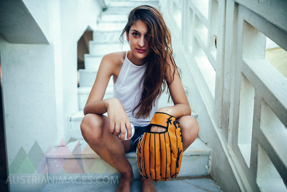 Young woman sitting on steps with ball and baseball glove