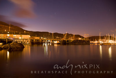 Night shot of sailing boats in harbour under starry sky, lights reflected in water