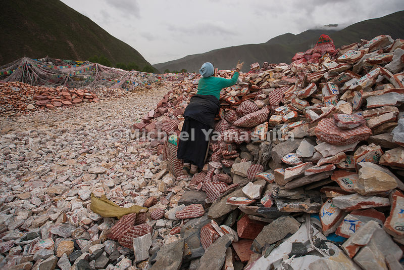 A woman adds her prayers to the growing mountain of more than a billion mani stones at Gyanamani Temple, in Yushu, an area rocked by earthquakes in 2010. This collection of hand-carved stones with Buddhist sutras and symbols is the largest in the world.