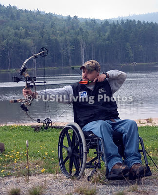 Male wheelchair archer by a lake