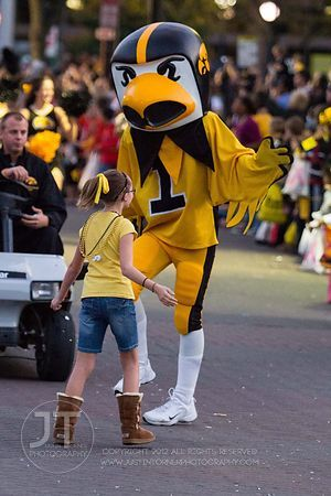 Herky the Hawk and a parade spectator dance on Clinton St during  the  University of Iowa homecoming Parade in Iowa City on Friday September 28, 2012. (Justin Torner/Freelance)