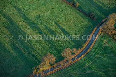 Aerial view of country lane winding through fields, England, UK.