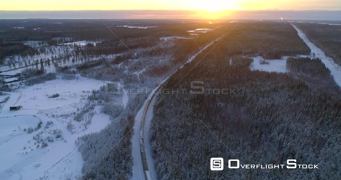 Train in Finnish Winter, Aerial, Tracking, Drone Shot, Following a Cargo Locomotive, in a Snowy Forest, Towards the Scandinavian Wilderness, on a Sunny, Wintry, Evening, in Uusimaa, Finland
