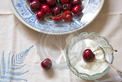 whole cherries on blue ceramic plate, on leaf linen and cream or yogurt in glass dish