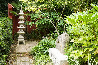 Chinese granite pagoda in the Red Wall garden planted around with palm Trachycarpus wagnerianus and Edgeworthia chrysantha. 'Holding hands stone' on plinth in foreground surrounded by bamboo, Fatsia japonica and Cladrastis sinensis. Beggars Knoll, Newtown, Westbury, Wiltshire, UK