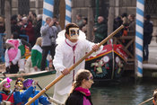 Man in White Costume and Bauta Mask Rowing in the Venice Carnival Water Parade  on the Rio di Cannaregio Canal