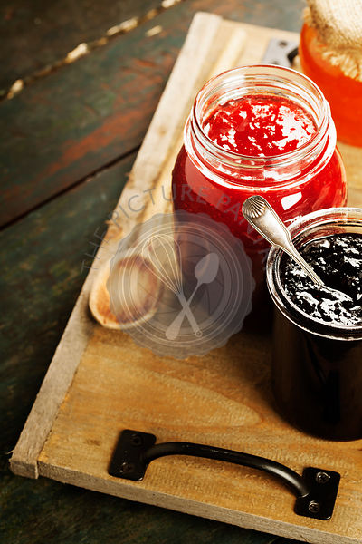 Fruit and berry jam with ingredients on a wooden background