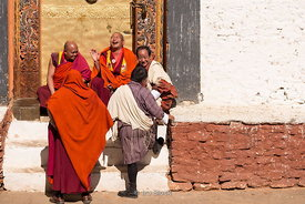 Monks and local men sitting on the stairs at Punakha Dzong festival in Bhutan.