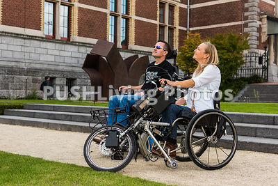 Couple using power wheelchairs admiring statues in a courtyard garden