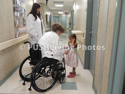 Female doctor in a wheelchair treating a young family