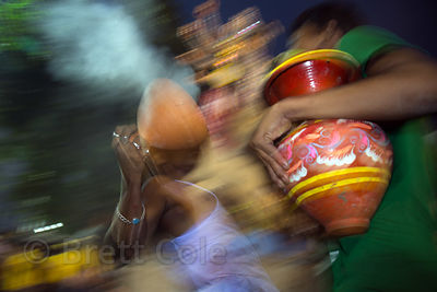 A family offers prayer in the form of dancing with smoking ghatam clay pots during the Durga Puja festival, Babughat, Kolkata, India