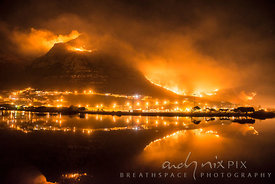 Night scene of huge bright orange flames covering mountain at night, reflected lake