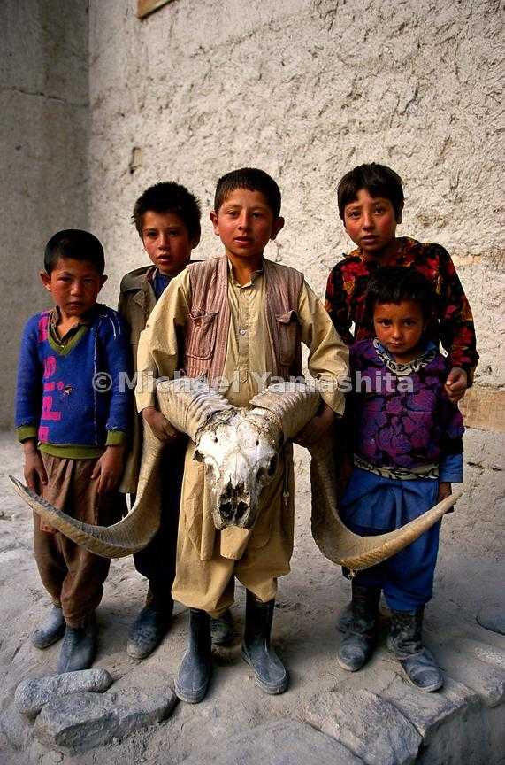 A group of children display the skull of an Ovis poli (Polo's Sheep)
