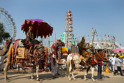 A parade goes past a carnival during the Pushkar Camel Fair, Pushkar, Rajasthan, India