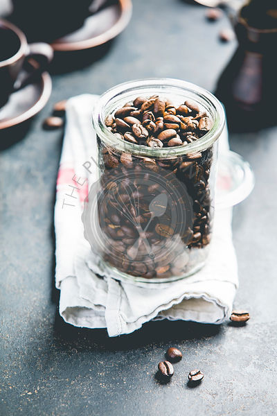 Coffee composition on dark background. Coffee beans in glass jar, coffee cups and old metallic coffee maker