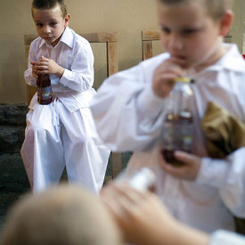 Boys in traditional costume drink soda from bottles during a folk event in Pecs, Hungary