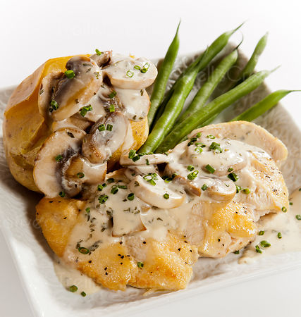 Sliced chicken breast topped with mushrooms and a creamy cheese sauce