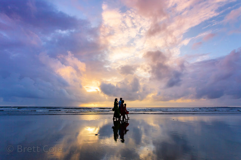 A family walks on Juhu Beach in Mumbai, India at sunset, with clouds reflecting in the Arabian Sea.