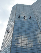 Four window washers on tall glass skyscraper