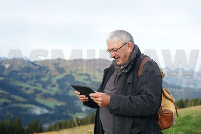 Senior man hiking in the mountains checking his way on a digital tablet