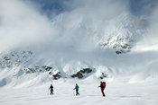 Group of skiers under steep mountain face