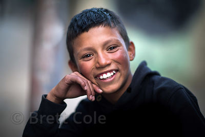 Candid street portrait of a boy in Leh, Ladakh, India, showing typically sunburned cheeks from the extremely intense sun in Leh