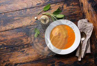 Pumpkin soup with sage on wooden background Copy space