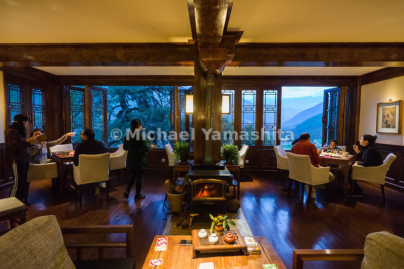 "Guests at the Songtsam Tacheng lodge dine on indigenous dishes—including yak meat—by windows open to deep mountain valleys. The lodge sits at an altitude of almost 10,000 feet. ""Pine-scented incense filled the air,"" says writer Scott Wallace. ""Upstairs, floating candles blazed in water-filled urns."""