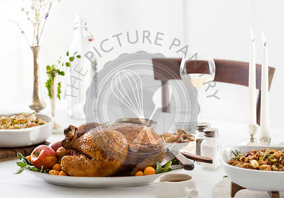 A beautiful, roast chicken holiday dinner on a clean white table with clean, yet rustic, settings.