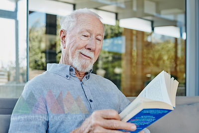 Senior man sitting on terrace reading book