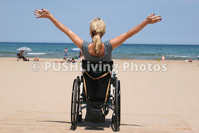 Woman in a wheelchair enjoying a sunny afternoon at the beach