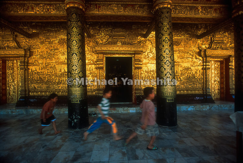 Taking their surroundings in stride, local boys flash past the gold walls of Wat Mai, an 18th-century temple adorned with scenes from the life of Buddha. The World Heritage designation covers the entire town of Luang Prabang, a former royal capital with structures deemed worthy of global celebration and protection.