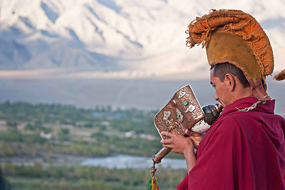 A monk plays a conch shell trumpet in a monastery in Ladakh.