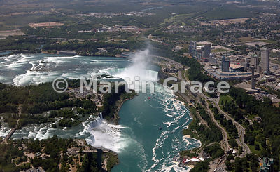Niagara Falls from the air, looking over Niagara River to American Falls, Bridal Veil Falls and Goat Island (left - USA); Canadian Horseshoe Falls (centre) and Niagara Falls city (Canada)