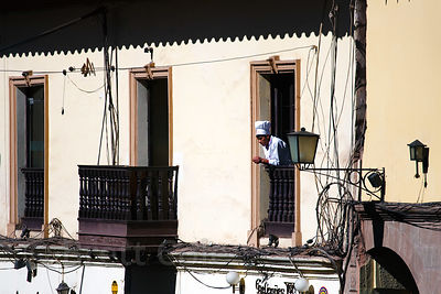 A chef watches a parade from a window in Cusco, Peru
