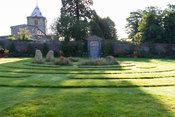 A grass maze with central stones occupies the centre of the Collector Earl's Garden, designed by Julian and Isabel Bannerman, with the Fitzalan Chapel seen beyond. Arundel Castle Gardens, Arundel, West Sussex, UK