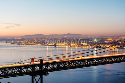 25th of April Bridge over the Tagus river (Tejo river) and Lisbon at twilight. Portugal