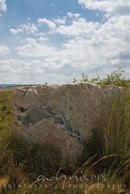 Vredefort Dome World Heritage Site, Freesate/Northwest Province, South Africa. A block of quaried rock composed of light and dark grey granite in a field of grass.