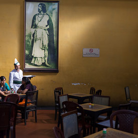 A waiter serves schoolgirls beneath a portrait of Rabindranath Tagore in the Indian Coffee House, Kolkata